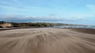 A large empty beach with a headland ahead and a choppy sea to the right. Blue sky and a little cloud above.