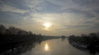 A hazy sun rising in a blue and cloudy sky. The Thames river is below, lined by trees.