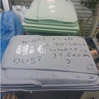 "Dust on large bins. Someone has written ""What is all this dust and where is it from?"" in the dust."