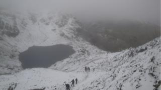 A foggy view of a lake between two snow covered mountain sides. People are walking on one side.