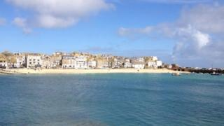 Blue water and a sandy beach with houses behind. Blue sky and a few clouds above.