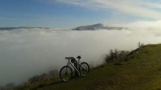 A mountain bike on grass in the foreground. A thick layer of fog behind and clear blue skies above. Mountain tops poking out of the fog.