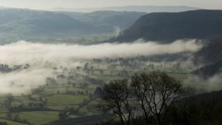 Lines of low mist in a valley. Trees and fields can be seen. Hazy, grey sky above.