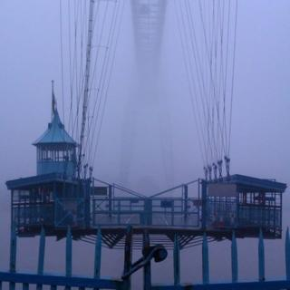 A large structure with wires going up to a bridge can just about be seen in the fog.