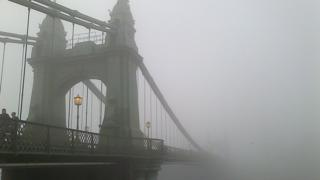 A view of an arch of the entrance to a bridge. Lamps are on and mist surrounds the scene. People walking on the bridge.