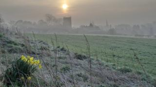 A misty view of a church and town. The sun is rising and there's grass and daffodils in the foreground.