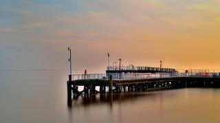 A yellow and peach misty sky behind a pier.