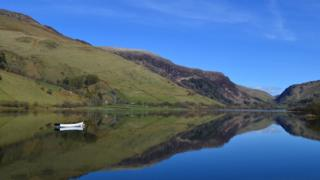 A calm lake with a small white boat on it. Surrounding are green and brown hillsides and blue sky above.
