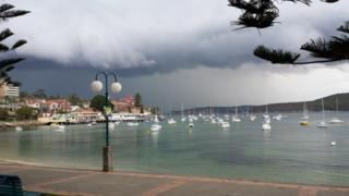 Light and dark grey clouds over a bay with boats in.