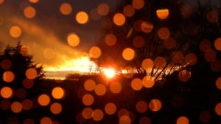 Orange water droplets on a window, a sun setting behind.