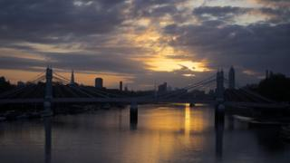 A calm river Thames, with a dark skyline behind. Albert Bridge can just about be seen in the light. A yellow patch in grey cloud indicating dawn.