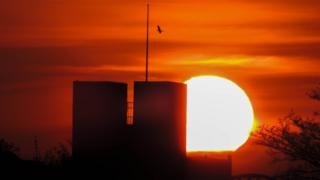 An orange and yellow sky with the sun setting behind a building. The building has two distinctive towers with a flagpole at the top. A bird flies near the flagpole.