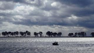 Grey cloud over grey water. A boat with two people in it is on the water. A line of dark trees divides the cloud and the water.