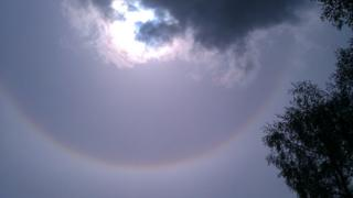 A halo around the sun, which is partly covered by cloud.