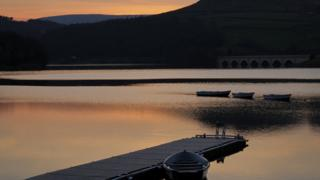 A light orange sky over a lake. Dark hills and three boats in the foreground.