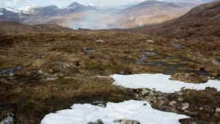 Part snow covering grassy mountains in Glencoe, Scotland.