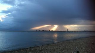 Heavy blue clouds hanging over the sky with three bursts of sun rays shining through. Overlooking the sea and Gosport town on the horizon.