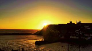 Bright yellow sunset peeking out from behind the cliff, overlooking the sea and houses on the cliff.