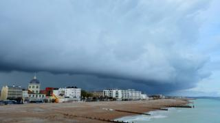 Dark blue/black clouds looming over Worthing beach and town. The sea is lapping against the beach, a bright aqua colour.