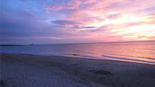Sunrise over the beach, the sky blue on the left hand side, graduating into colours of pink and yellow on the right. The colours of the sky reflect off the sea, turning it an orange colour.