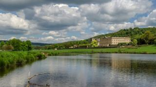 White clouds with patches of dark grey in blue sky loom above green countryside and a large stately home on the right hand side. In the foreground is a lake and the shadow of the house reflects off the water.