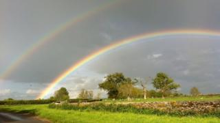 Double rainbow over a green field and concrete road. Colours of the rainbow include purple, blue, green, yellow, orange and red.