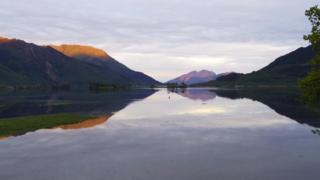 Grey skies over mountains on either side of the picture, green at the base and glinting orange at the top from the morning sunrise. A large lake stretches from the foreground to the background, the colours of the mountains reflecting in the water.