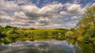 Rolling green hills in the background, with bright yellow rapeseed fading into the background. The bright green reflects in the reservoir water. Blue sky dotted with white and grey clouds.