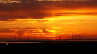 Bright yellow, orange and red sky beaming over the sea and beach in darkness in the foreground. About twenty three wind turbines in diagonal lines stretch from the centre of the photo into the background.