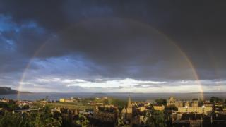 A large full rainbow stretching over a small town in the foreground and the sea in the background. The rainbow includes colours of red, blue, purple, orange, yellow and green.
