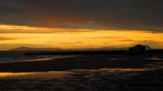 A bright yellow sky over a darkened beach in the shadow of the sunset. A dark row of rocks protrudes into the sea, the water lapping at the beach shore.
