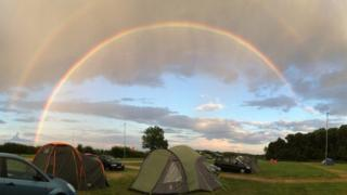 A double rainbow arching over a campsite, two tents pitched and two cars positioned in the field. The rainbow includes colours of red, orange, yellow, blue, green and purple.