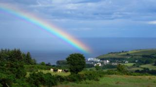 Wide rainbow reaching from the left hand side of the photo, disappearing into the blue sea. Green fields and trees on rolling hills lie in the foreground, with a few horses grazing in a field. The rainbow includes colours of purple, blue, yellow, orange and red.