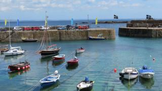 Light blue sky with a few pale white clouds hovering over the clear blue water. About nine boats of various shapes and sizes are anchored in the harbour, many with brightly coloured flags attached to them. A pier divides the harbour and the rest of the sea. A few cars of different colours are parked on the pier.