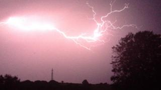 The sky is a pink colour as it draws towards sunset, illuminating the staggering lightning flash through the middle of the picture. The lightning branches off at the end, spreading across the right hand side of the frame.