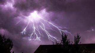 The clouds covering the sky are a deep purple colour, with the lightning flash exploding from the centre. The lightning branches out, stretching towards the darkened tree tops below.