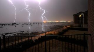 Taken from a residential property, a black railing and pathway lies in the foreground, overlook a grey sea and bright lights of a neighbouring town in the background. Three lightning flashes descend from the top of the photo and disappear behind the sea. The flashes are white and branch off in various places.