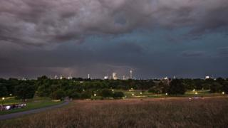 Dark grey clouds over the vast green park in the foreground. The London skyline can be seen in the far distance, lit up by the sunset. Three thin lightning flashes appear in the distance over the skyline.