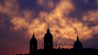 Dark silhouette of St Paul's in the foreground. The sky is a dark purple colour with scattered clouds, a bright yellow colour from the beam of the sunset.