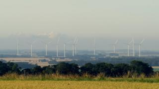 Green fields in the foreground, stretching into the far distance. The sky is a grey colour yet bright, from the hazy sunshine of the morning. About twelve tall, white wind turbines stand mid photograph.
