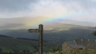 Rolling green hills in the in the background, underneath a low and grey sky. A wooden signpost stands in the centre, pointing left. Just behind the signpost there is a faint strip of rainbow, with colours including orange, yellow, turquoise, purple and red.