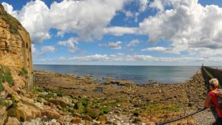 Blue sky with sporadic cloud over an aqua colour sea. In the foreground are rocks and small rock pools and a tall cliff face frames the shot on the left hand side.