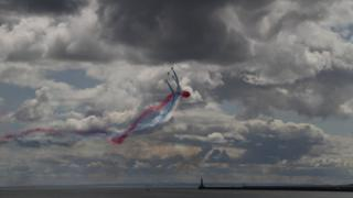 Dark grey storm clouds over a grey sea. Four jet planes are flying into the foreground, emitting brightly coloured smoke behind them in blue, red and white. The smoke trails create an impressive twisted pattern in the sky.