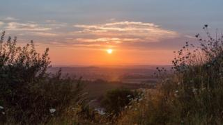 Green bushes frame the picture in the foreground, looking down onto green hills that slowly disappear onto the horizon. The orange sunset is low in the sky, spreading an orange, yellow and pink colour across the skyline.