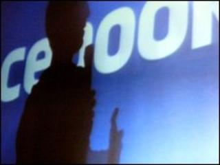 silouthette of someone in front of facebook sign
