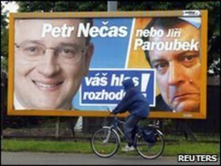 A man bicycles past an election poster for the Civic Democratic Party, featuring leader Petr Necas (left) and leader of the opposing Social Democrats Jiri Paroubek (right).