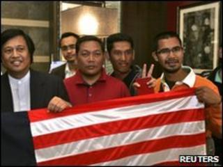 Malaysian activists pose with their national flag upon arrival in Amman