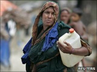 A woman carries a container of water in Satkhira, Bangladesh, in May 2010