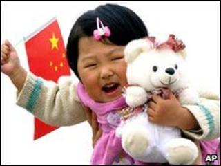 Child carrying Chinese flag and teddy bear