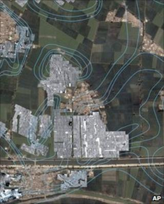 Satellite image with radar imaging showing the outlines of streets, houses and temples underneath the green farm fields and modern town of Tel al-Dabaa in Egypt